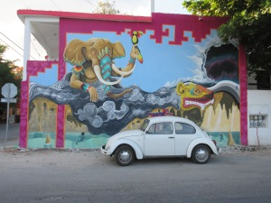 Retro Beetle against a mural backdrop in Tulum